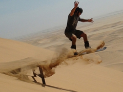 Robby jumps on his first attempt at sand boarding; Swakopmund