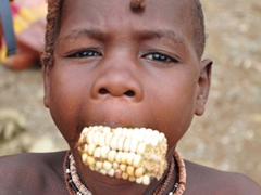 A Himba child munches on some corn; Ohungumure Village
