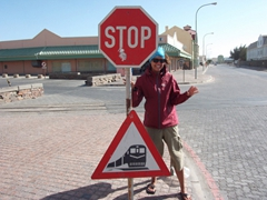 "Becky posing next to a ""caution, yield to train"" sign; Luderitz"