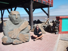 Robby poses beside a huge stone statue underneath The Tug Restaurant; Swakopmund