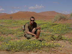 Robby strikes a pose amidst a field of yellow flowers; Sossusvlei
