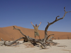 Robby stands on a petrified tree in the Dead Pan; Sossusvlei
