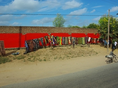 Colorful wraparound cloths for sale against a vibrant red backdrop