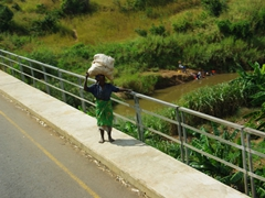 An elderly woman struggles with her heavy load