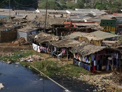 Clothing stalls next to a polluted river