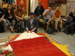 Sipping mint tea while watching a carpet and blanket demonstration; Fes medina