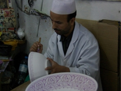 Artisans hard at work creating ceramic ware; Fes