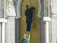 Workers using lemons to scrub the bronze doors of the Fes Royal Palace
