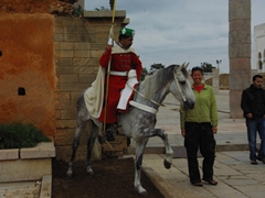 Becky poses next to a horseback guardsman; Rabat's Hassan Tower complex