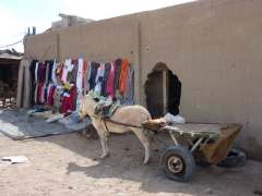 A donkey cart rests by a hole in the wall; Nouadhibou