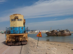 An old train slowly saunters by at the Nouadhibou ship graveyard