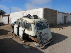 Wreckage of a car on the pavement of a main street in Nouadhibou