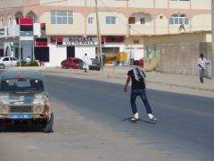A youth roller skates down the main street in Nouadhibou
