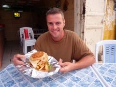 "Robby grins as he tears into a Nouakchott legend, the Ali Baba ""Big Burger"""