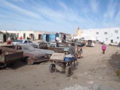 A fisherman pulls a handcart through the parking lot of Nouadhibou's main fishing port