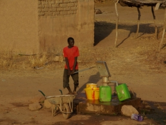 A village boy working the water pump, a manually intensive chore