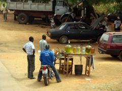 A motorcyclist stops to buy cheap roadside petroleum (entrepreneurial Béninois buy cheap fuel from neighboring Nigeria and smuggle it across the border to earn a bit of extra income)