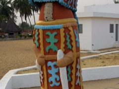 Colorful figurine at the Door of No Return monument; Ouidah