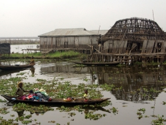 A pirogue passes by a leaning stilt house; Ganvie