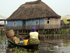 A classic shot of a Ganvie resident navigating her way through the village