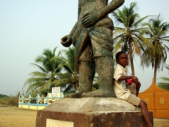 Young boy sits on the base of one of the statues along the Route des Esclaves; Ouidah