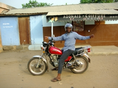 A friendly local man stops his motorcycle to pose for a photo and then continues on his way; Ouidah
