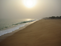 Strong waves crashing against the beach near the Door of No Return monument; Ouidah
