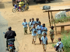 School children walking along the street side around lunch time; near Ouidah