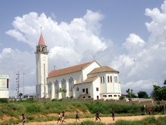 Boys playing soccer in a field below a Cabinda Cathedral