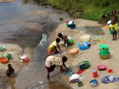 A family washing dishes and laundry in a stream; near Dondo