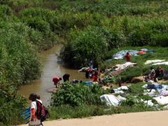 Lubango villagers washing laundry in the river while school kids lug their chairs from school