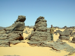 Robby standing next to weathered rock formations; Djanet