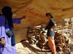 Abdallah points out some cave paintings to Becky; Idaren Valley