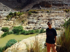 Becky poses beside a guelta; Idaren Valley