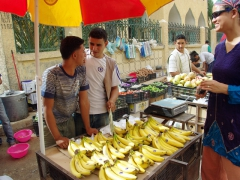 Becky laughs as the fruit vendors urge her to take their photo; El Oued marketplace