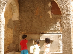Children collecting water from a public fountain; Ghardaia