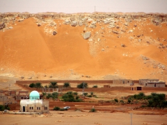 A simple mosque is dominated by the nearby sand dunes; El Golea