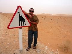 """Robby poses next to a """"caution...camel"""" sign; Algerian Sahara"""