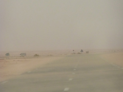 Sand blowing over the highway during a stand storm; Grand Erg Occidental