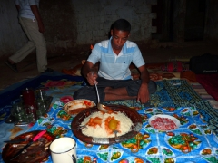 Salim pours sauce over our couscous dinner; Yousef's house in El Golea