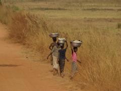 Young girls walking the side of the road; near Chutes de Karfiguela