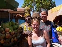 Ruth and Becky posing next to a watermelon vendor in Bobo-Dioulasso during cook group shopping duty