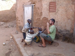 Kids clamoring to have their photo taken while Robby struggles to comply; old village of Kibidoue