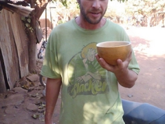 Robby takes a swig of the local brew; old town of Kibidoue in Bobo-Dioulasso