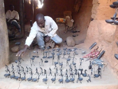 A blacksmith proudly showing off his wares; old village of Kibidoue