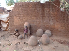 A child is dwarfed by the massive clay pots in the old village of Kibidoue