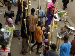 Stick vendors selling massive mortar and pestles at Kumasi central market