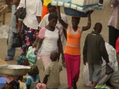 An overloaded vendor carefully threads her way through the chaotic Kumasi market