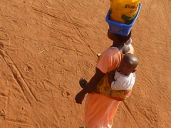 A quintessential image of Africa...a lady with a baby on her back while balancing a bucket on her head
