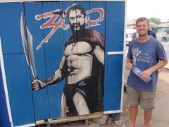 Robby poses beside a 300 shack painting in Accra